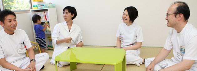 テーブルを囲み談笑をする4人の医師の方々